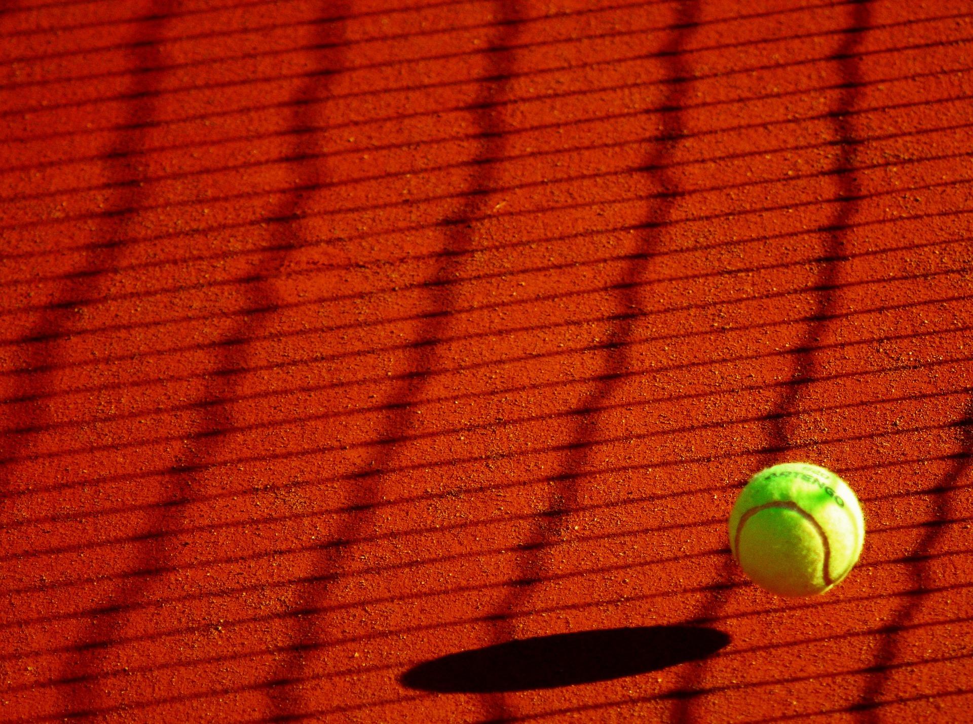 Tennisball auf rotem Platz
